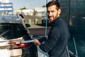 Vista vertical de cintura para arriba del hombre caucásico sosteniendo equipo especial y sonriendo a la cámara mientras limpia el automóvil con agua a alta presión. concepto de lavado de coches. enfoque selectivo foto