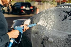 Primer plano horizontal de coche negro con espuma de limpieza en el servicio de lavado de coches al aire libre con pulverizador de alta presión. concepto de coche limpio al aire libre foto