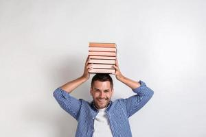 Funny happy young man holding books on his head. Back to school- Image photo