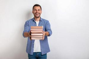 Portrait of happy young man holding books in his straight hands. Back to school photo
