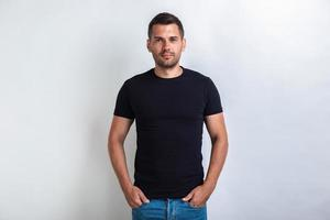 Nice man wearing in black t-shirt standing holding his arms in pocket, seriously looking at the camera photo