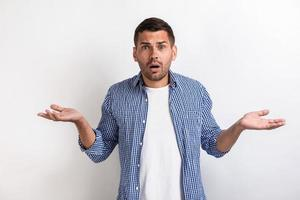 Handsome amazed man standing with surprised look and hands apart in studio photo