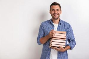 Portrait of happy nerd young man holding books in his hands. Back to school photo