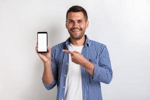 Smiling man holding a smartphone and pointing to screen - Mockup image of white empty blank screen of phone photo