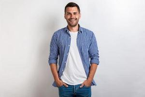 Nice man wearing in casual clothes standing holding his arms in pocket, smiling and looking at the camera photo
