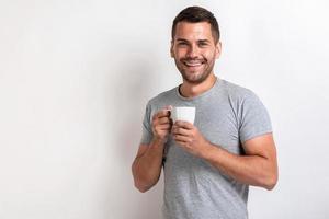 Hombre sonriente se encuentra con una taza de té o café por la mañana y mirando a la cámara.- imagen foto