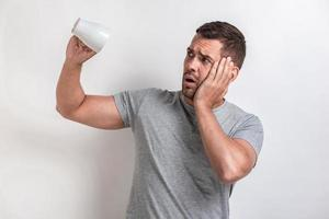 Sadly man flips an empty cup and looking unhappy, touches on cheek.- Image photo