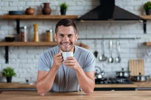 Handsome man sits at the kitchen table with cup of morning tea or coffee and smiling looking at the camera photo