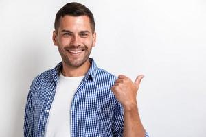 Handsome happy man pointing by his big finger backward and looking at the camera.- Image photo