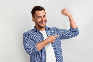 Happy man laughing and pointing for his biceps by his arm.- Image photo