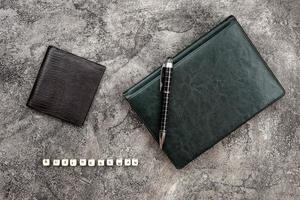 cuaderno de cuero de vista superior acostado sobre un fondo de yeso. empresario de inscripción foto