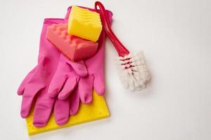 Sponge, household brush, latex gloves lying on a white background. Concept cleaning service photo