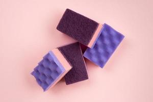 Kitchen sponges for washing dishes and other domestic needs on pink background photo