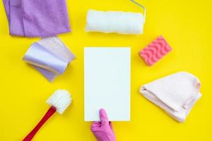 Cleaning items and a clean layout lie on a yellow background. Cleaning service concept. photo
