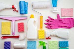 Cleaning items are laid out on a white surface photo
