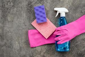 household accessories, washing spray, spongy and latex gloves lying on a gray decorative plaster background. photo