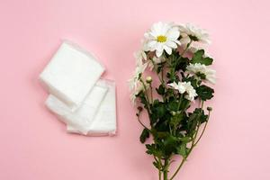 Feminine gasket for menstruation and white flower on a pink background. photo