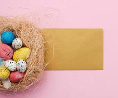 Easter eggs in nest and greetings card on pink background photo