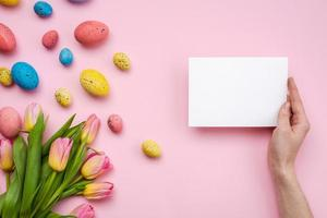 Easter eggs and greetings card on pink background photo