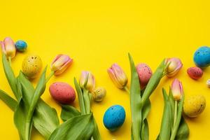 Easter eggs and colorful tulips on yellow background. Top view with space for your greetings photo