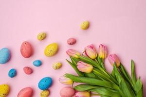 Fondo de Pascua, huevos multicolores y ramo de tulipanes se encuentran en una mesa rosa blanca. - copia espacio foto