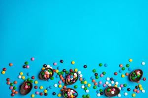 huevo de pascua de chocolate con colorida explosión de caramelos y dulces sobre un fondo azul. endecha plana. vista superior foto