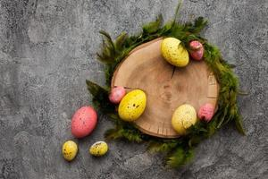 Colorful, easter eggs around wooden stand on pink background photo