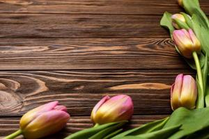flowers of spring tulips on the wooden boards of the table. Greeting card for mother's Day, Easter. Copy space photo