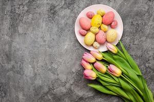 sobre un fondo de yeso gris hay hermosos tulipanes y un plato con coloridos huevos de pascua. copia espacio foto