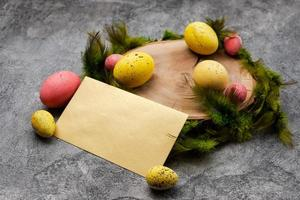 Empty mockup  blank on a  Easter background. Colorful eggs and feathers on the wooden stump. - Copyspace photo