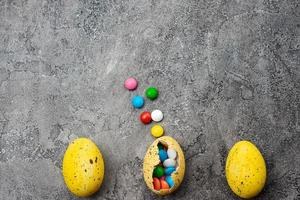 Multi-colored candies in the yellow egg  on a grey plaster background. - Copyspace photo