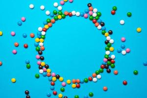 Easter background with multi-colored candy lie on a blue background. -Circle copyspace photo