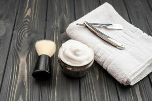Imagen de herramientas de afeitar, cepillo, espuma, afeitadora sobre fondo oscuro de madera foto