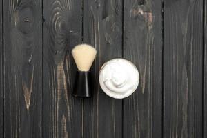 Brocha de afeitar y crema sobre fondo de madera oscura. foto