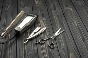 herramientas de corte de pelo de los hombres sobre un fondo oscuro de madera. foto