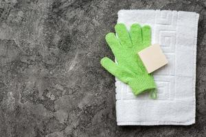 Soap, shower towel, bath mitten on gray, plaster flat lay background with copy space. Hygiene concept. photo