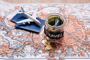 Holidays budget concept. Holidays money savings in a glass jar with aircraft toy on world map photo
