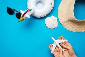 On a blue background are a hat, sunglasses, an oversized circle, in the hands of an airplane photo