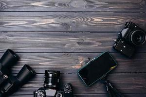 Devices are laid out on a wooden table cameras, smartphone, binoculars. Place for advertising photo