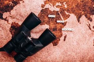 Black binoculars lies on the a geographical map photo