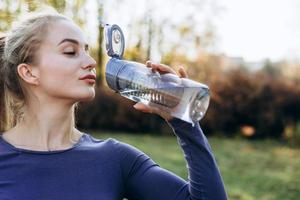 Slim sporty girl drinking water. Fitness young woman taking break after training in park. photo