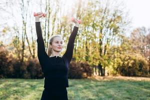 A young woman goes in for sports outdoors. girl with blond hair is training in the park on the nature. photo