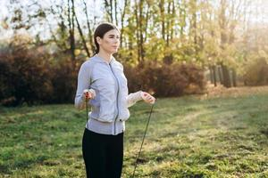 Pretty, slim girl jumping on skipping rope outdoors photo