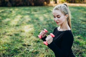 Girl with dumbbells training outdoors photo