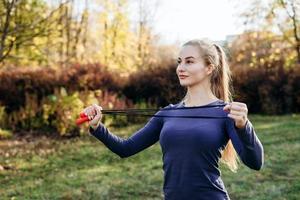 sonriente, hermosa chica rubia haciendo saltar la cuerda al aire libre foto