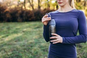 joven atlética abriendo una botella de agua mientras hace ejercicio al aire libre, al aire libre. copie el espacio. foto