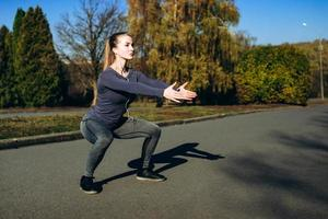 Girl in sportswear and headphones doing sit-ups while training outdoors. photo