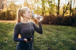A young, pretty girl in headphones drinks water after a workout. photo
