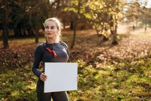 Sporty girl holding a blank sheet outdoors photo