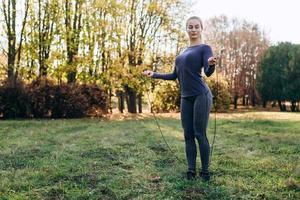 Chica bonita y delgada saltando sobre la cuerda de saltar al aire libre foto